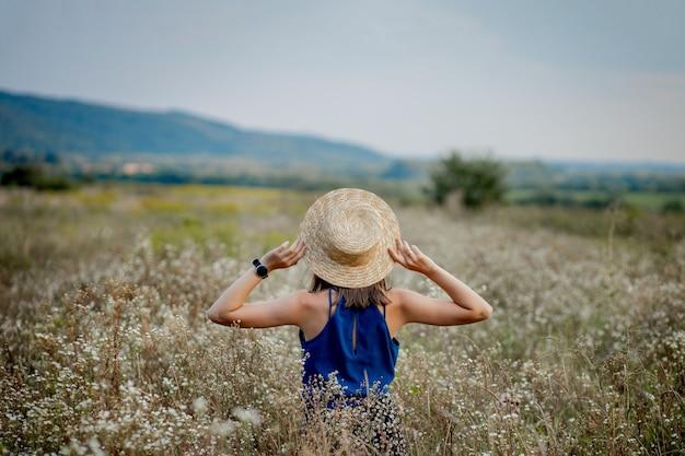 Copyspace を離れて見ている野の花のフィールドに滞在する女性。スタイリッシュな服と帽子をかぶった魅力的な若い女の子のブルネットの笑顔が、農業の花の谷に滞在します。カントリーサイドプレイスのかわいいお嬢さん。