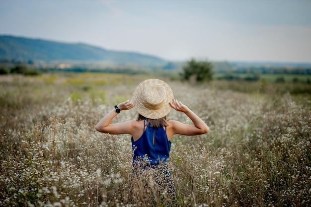 Copyspace をよそ見野生の花のフィールドに滞在する女性。スタイリッシュな服と帽子をかぶった魅力的な若い女の子のブルネットの笑顔が、農業の花の谷に滞在します。