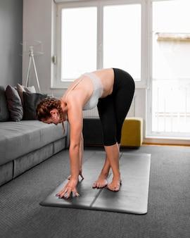 Женщина остается на коврике для йоги