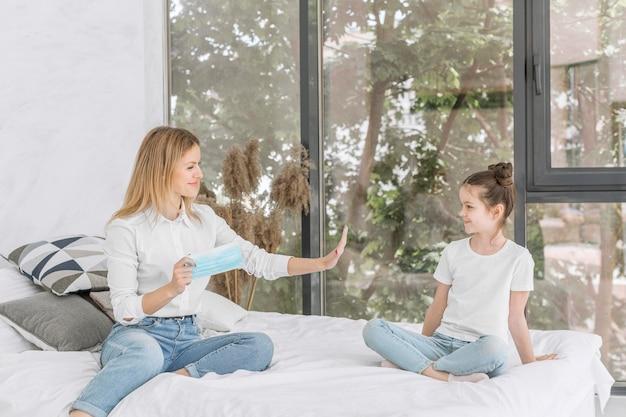 여자는 침대에 그녀의 딸과 함께 체재