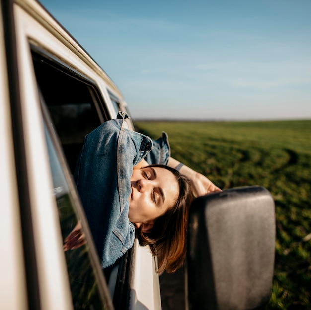 Woman staying with her head out of a van