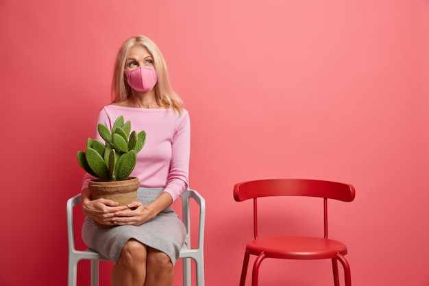 女性は自己隔離で一人で家にいる 保護フェイスマスクを着用し、コロナウイルスの拡散を防止する 鍋にサボテンを持ち、ピンク色で隔離された椅子に座る Premium写真