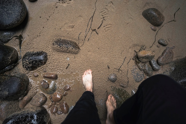 Woman stepping on a sandy beach at plemont bay, isle of jersey