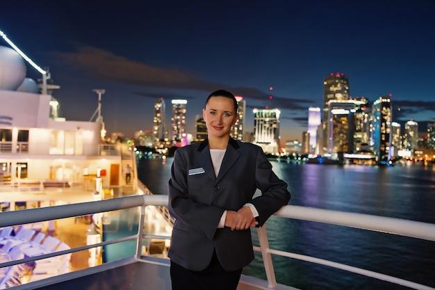 アメリカ、マイアミの夜の船上での女性スチュワード。街のスカイラインのスーツジャケットの官能的な女性。水上輸送、輸送。ビジネスのための旅行。放浪癖、冒険、発見、旅。