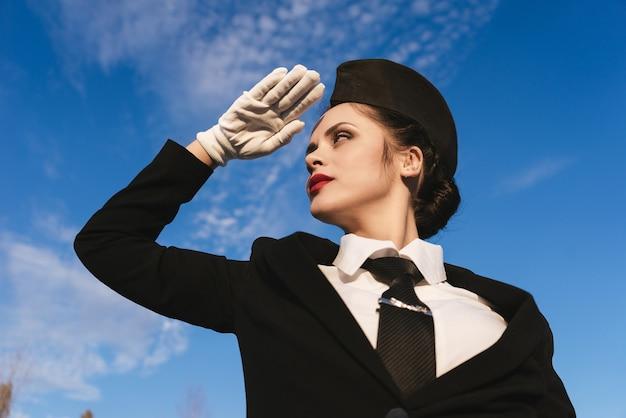Woman stewardess in uniform against the blue sky