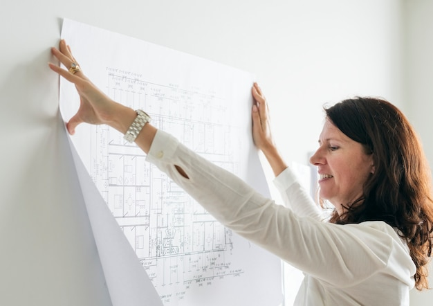 A woman sticking a blueprint to the wall