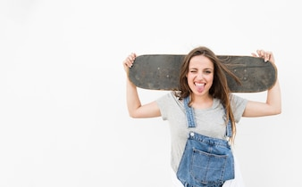 Woman sticking her tongue out holding skateboard on her shoulder against white backdrop