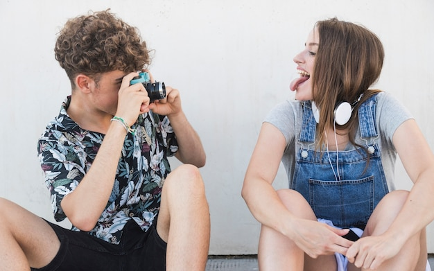 Woman sticking her tongue out while her boyfriend taking photograph with camera