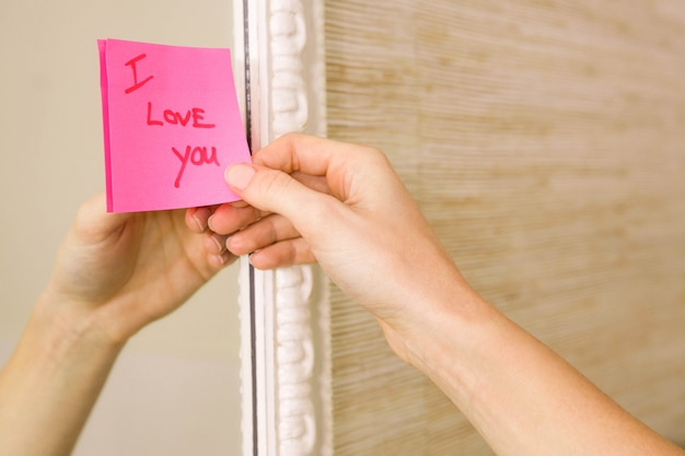 Woman sticking i love you word sticky note on mirror