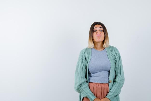 Donna che attacca fuori la lingua in abiti casual e guardando divertente, vista frontale.