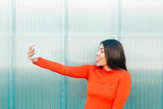 Женщина торчит язык, принимая селфи на смартфон