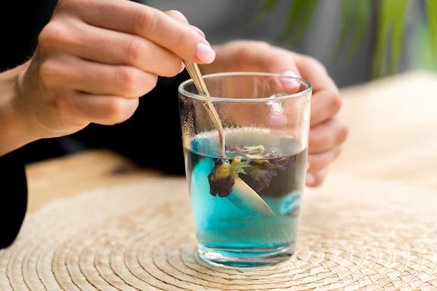 Woman stirring blue tea in glass