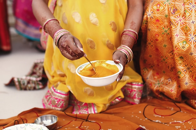 Woman stirs turmeric paste in the white bowl