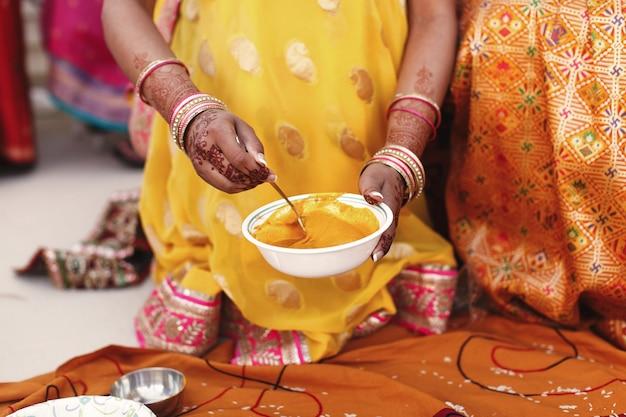 La donna mescola la pasta della curcuma nella ciotola bianca