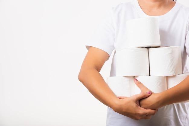 Женщина держит в руках много рулонов туалетной бумаги на груди