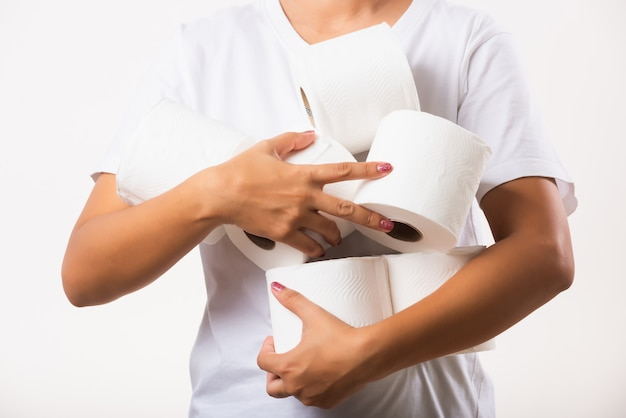 Woman stocking up she holding many rolls of toilet paper in arms on chest