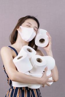 家の検疫用のトイレットペーパーを仕入れている女性は、トイレットペーパーのロールを手に持っています。
