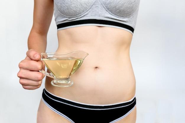 灰色の背景にオイルを両手で女性の胃。