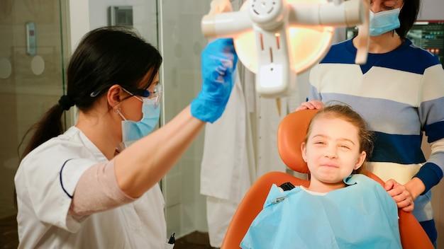 口腔病学の椅子に座っている小さな患者を検査するためにランプを点灯している女性の口腔病学者の技術者。看護師が検査のためのツールを準備している間、医者は歯の健康をチェックしている女の子に話します