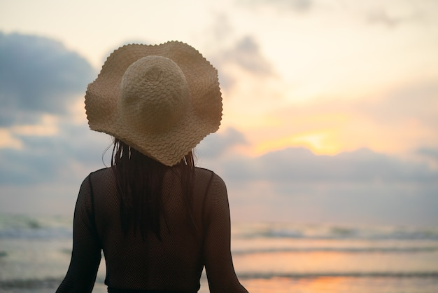 女性は立って、消える太陽を見ました。