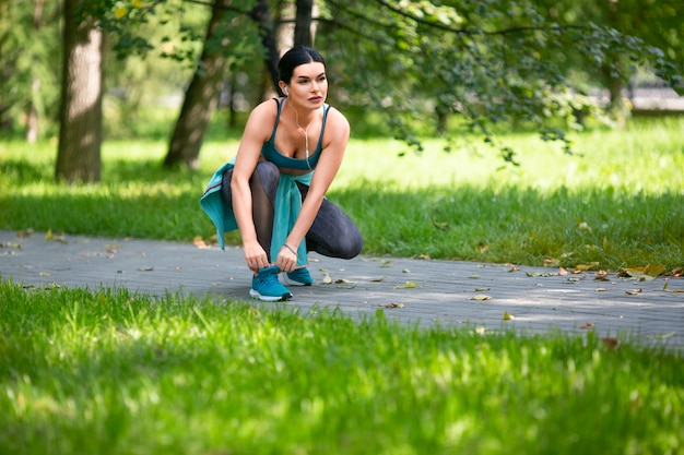 Woman stopped jogging in a city park to tie shoelaces