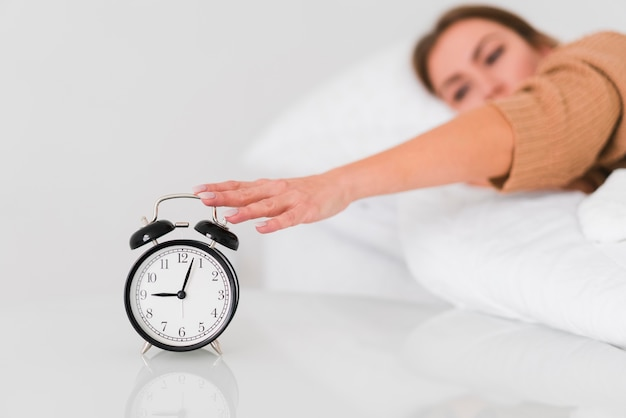 Woman stopping the alarm clock