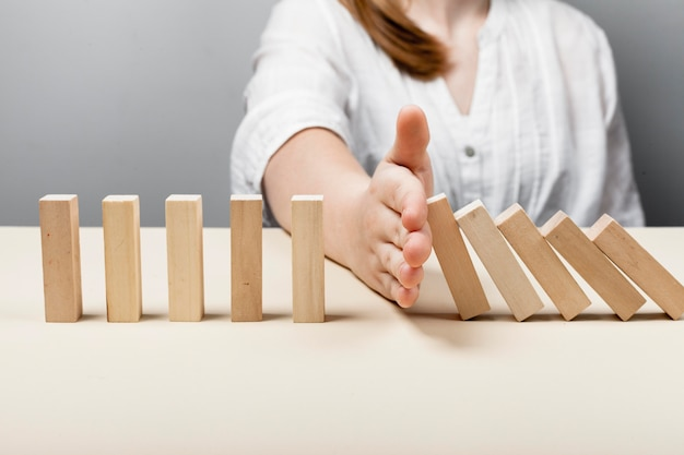 Donna che ferma i pezzi di legno del concetto di caduta