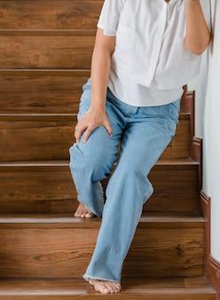 Женщина останавливается для отдыха и опирается на стену для поддержки, в то время как она не может подняться по лестнице из-за покалывания в ногах. понятие синдрома гийена-барре и болезни онемения ног или побочного эффекта вакцины.