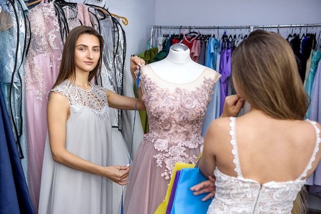 Woman in store thinking about buying of new dress