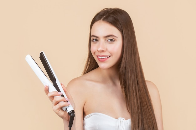 Woman straightening hair with straightener. portrait of beautiful girl using styler