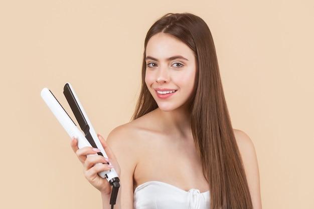 Женщина, выпрямляющая волосы с помощью выпрямителя. портрет красивой девушки с использованием стайлера