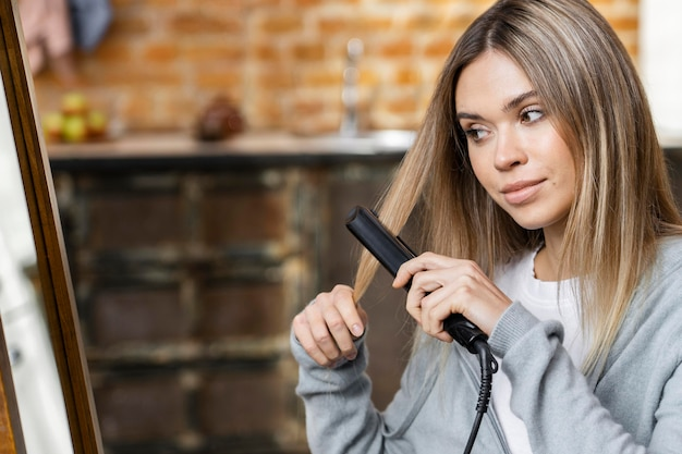 Woman straightening her hair at home