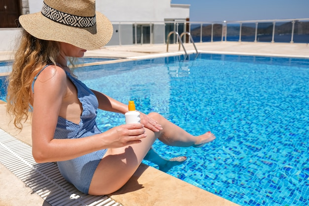 Woman in straw hat applying sun protection cream near swimming pool