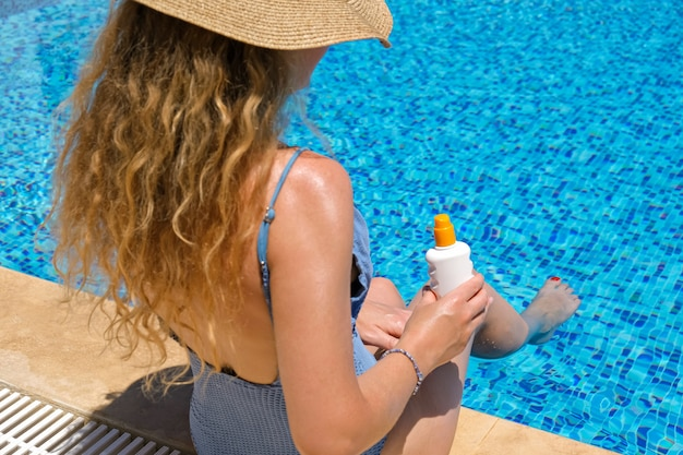 Woman straw hat applying sun protection cream sunscreen swimming pool