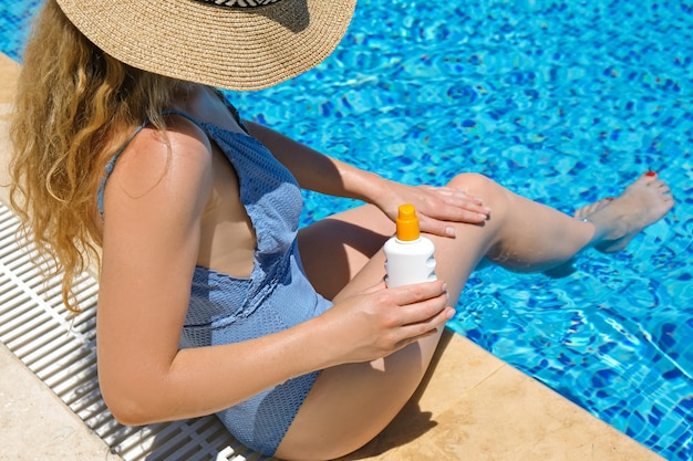 Woman in straw hat applying sun protection cream suntan  swimming pool at resort
