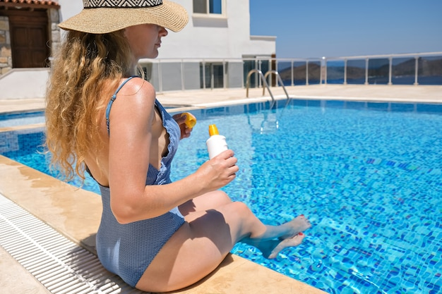Woman in straw hat holding sun protection cream sunscreen lotion near swimming pool