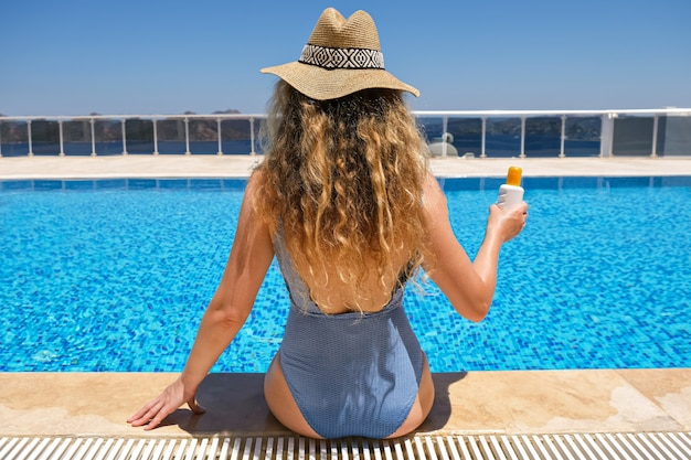 Woman in straw hat holding sun protection cream sunscreen lotion