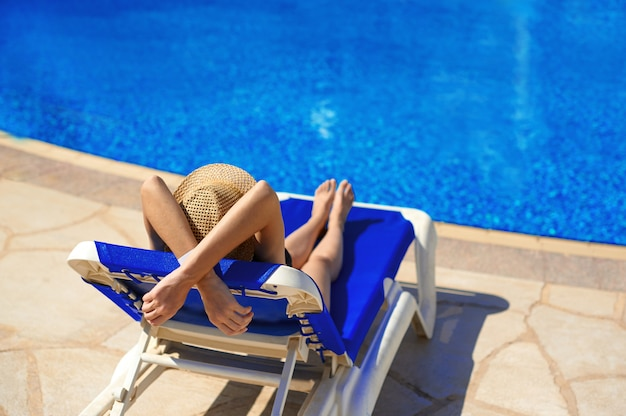 Woman in a straw hat relaxing on a deck-chair near a luxurious summer pool in hotel.