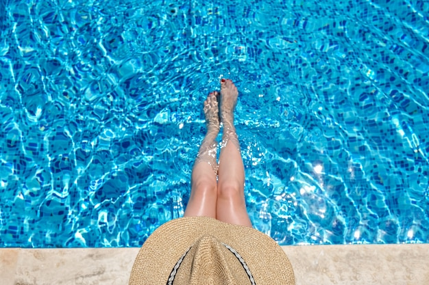 Woman in straw hat sitting in the swimming pool with legs in water