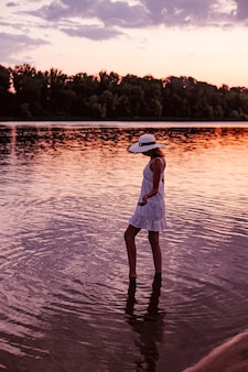 A woman in a straw hat at sunset. a beautiful young slender blonde stands in the water in a white summer dress and raises her arms to the sides.