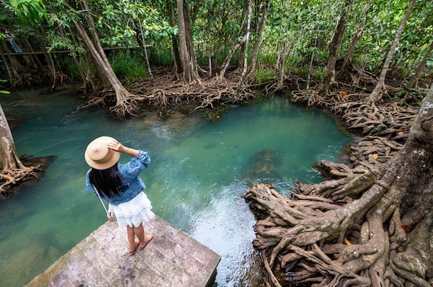 A woman, stream of water and beautiful root of trees at thapom klong song nam, krabi, thailand