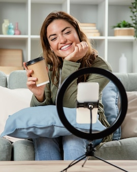 Woman streaming live while drinking coffee