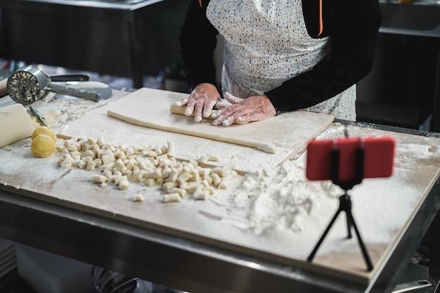 파스타 공장 내부에서 휴대전화로 뇨키의 온라인 이탈리아 요리 수업을 스트리밍하는 여성 - 손에 초점