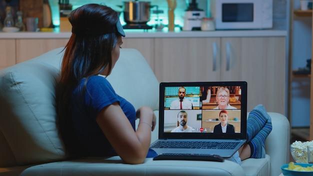 自宅から夜にオンラインウェビナートレーニングをストリーミングする女性。ノートパソコンの前でオンライン会議、ビデオ通話、ウェブカメラチャットを使用した同僚とのビデオ会議コンサルティングを行うリモートワーカー。