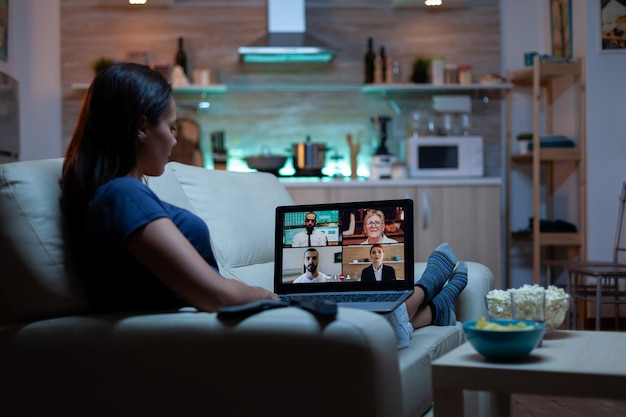 Woman streaming online webinar training at night from home
