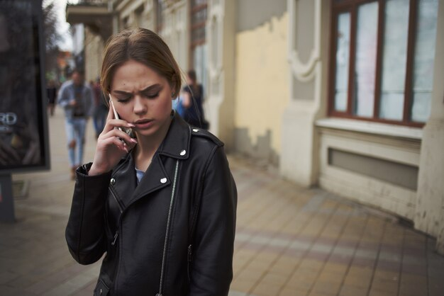 Woman on the street in a black jacket talking on the phone