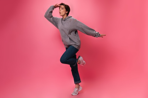 Woman in street style outfit looks into distance on pink background. active teen girl in jeans and hoodie jumping on isolated