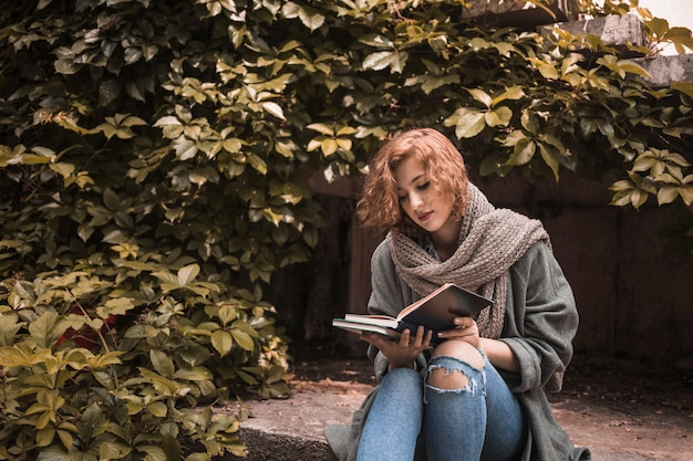 Woman in street wear sitting on board and attentively reading book near plant