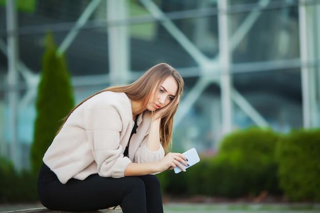 屋外に座っている間仕事から強調した女性