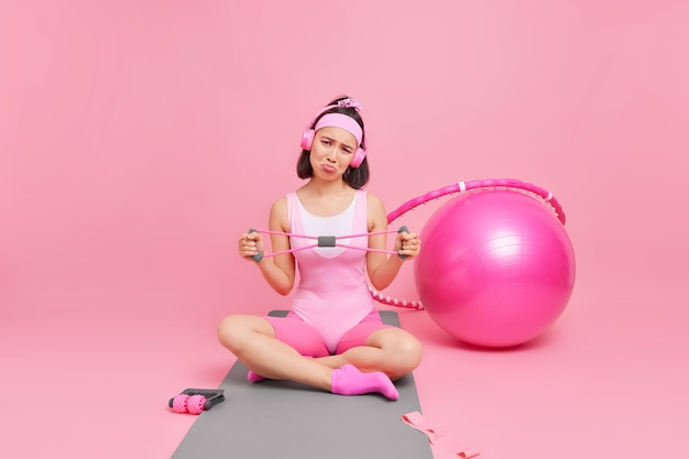 Woman stretches hands with resistance band dressed in activewear crosses legs on mat listens music via headphones surrounded by sport equipment. healthy lifestyle concept